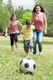 Familia que juega a fútbol y que se divierte imagen de archivo libre de regalías