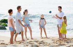 Familia que juega a juegos activos en la playa Foto de archivo libre de regalías