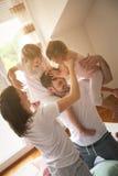 Familia que juega junto en cama Padres que pasan t libre Imagen de archivo libre de regalías
