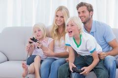 Familia que juega a los videojuegos Fotos de archivo libres de regalías