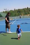 Familia que juega a tenis Foto de archivo