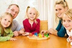 Familia que juega un juego de mesa Imagen de archivo libre de regalías