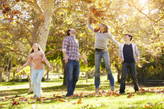Familia que lanza a Autumn Leaves In The Air Fotos de archivo libres de regalías