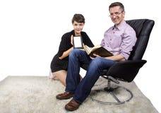 Familia que lee en casa Imagenes de archivo