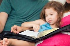 Familia que lee la biblia junto Fotos de archivo libres de regalías