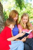 Familia que lee un libro Imagen de archivo