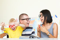Familia que lee un libro Imagenes de archivo