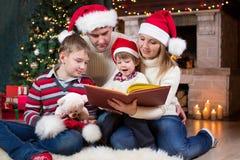 Familia que lee un libro delante del árbol de navidad Foto de archivo