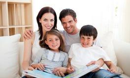 Familia que lee un libro en el sofá Fotos de archivo