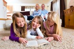 Familia que lee un libro junto Imagen de archivo