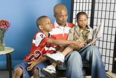 Familia que lee una historia fotografía de archivo libre de regalías