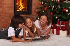 Familia que lee una historia en el tiempo de la Navidad Imagen de archivo libre de regalías