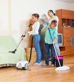 Familia que limpia con la aspiradora en casa Foto de archivo libre de regalías