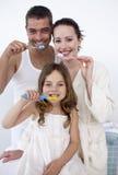 Familia que limpia sus dientes en cuarto de baño Foto de archivo