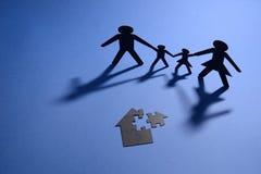 Familia que lleva a cabo las manos con la casa del rompecabezas Imagen de archivo