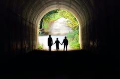 Familia que lleva a cabo las manos en el túnel Foto de archivo libre de regalías