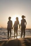 Familia que lleva a cabo las manos en la playa, puesta del sol Fotos de archivo libres de regalías