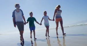 Familia que lleva a cabo las manos mientras que camina en orilla en la playa almacen de video