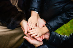 Familia que lleva a cabo sus manos juntas imagenes de archivo