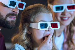 Familia que lleva los vidrios 3d que miran película y que comen las palomitas Fotos de archivo