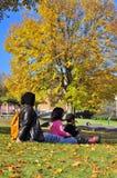 Familia que merienda en el campo mientras que mira follaje del otoño Imágenes de archivo libres de regalías