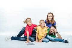 Familia que miente así como la tableta digital Imagenes de archivo