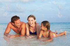 Familia que miente en el mar en día de fiesta tropical de la playa Foto de archivo libre de regalías