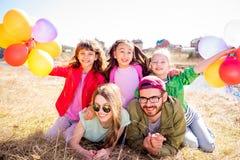 Familia que miente en hierba con los globos Foto de archivo