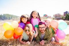 Familia que miente en hierba con los globos Fotografía de archivo libre de regalías