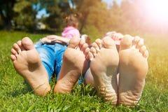 Familia que miente en la hierba por la mañana Foto de archivo libre de regalías