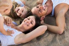 Familia que miente en la playa, visión superior Foto de archivo
