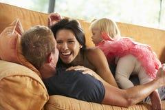 Familia que miente en Sofa At Home Imagenes de archivo