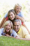 Familia que miente encima de uno a en un parque Imagen de archivo