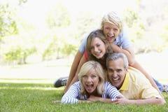 Familia que miente encima de uno a en un parque Fotos de archivo