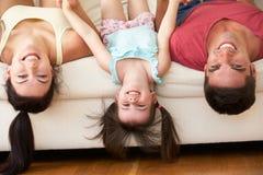 Familia que miente upside-down en el sofá con la hija Imagenes de archivo