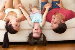 Familia que miente upside-down en el sofá con la hija Imágenes de archivo libres de regalías