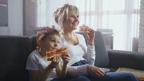 Familia que mira al programa de televisión cómico y que come la pizza metrajes