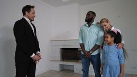 Familia que mira alrededor de casa con el agente inmobiliario almacen de video