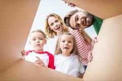 Familia que mira a escondidas de la caja de cartón fotografía de archivo
