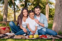Familia que mira la cámara mientras que pasa el tiempo en comida campestre junto Foto de archivo libre de regalías
