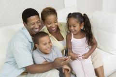 Familia que mira la imagen en el teléfono de la cámara Fotografía de archivo libre de regalías