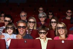 Familia que mira la película 3D en cine Imagenes de archivo
