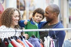 Familia que mira la ropa en el carril en alameda de compras Imágenes de archivo libres de regalías