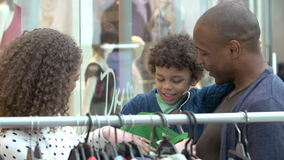 Familia que mira la ropa en el carril en alameda de compras almacen de metraje de vídeo