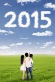 Familia que mira los números 2015 en el cielo Fotos de archivo libres de regalías