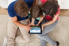 Familia que mira Mountain View sobre la tableta digital Imagenes de archivo
