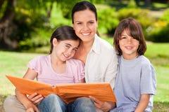 Familia que mira su foto del álbum Imagen de archivo libre de regalías