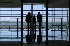 Familia que mira a través de la ventana Foto de archivo libre de regalías
