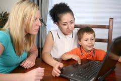 Familia que mira un ordenador Fotos de archivo libres de regalías
