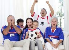 Familia que mira un partido de fútbol en la televisión Imagenes de archivo
